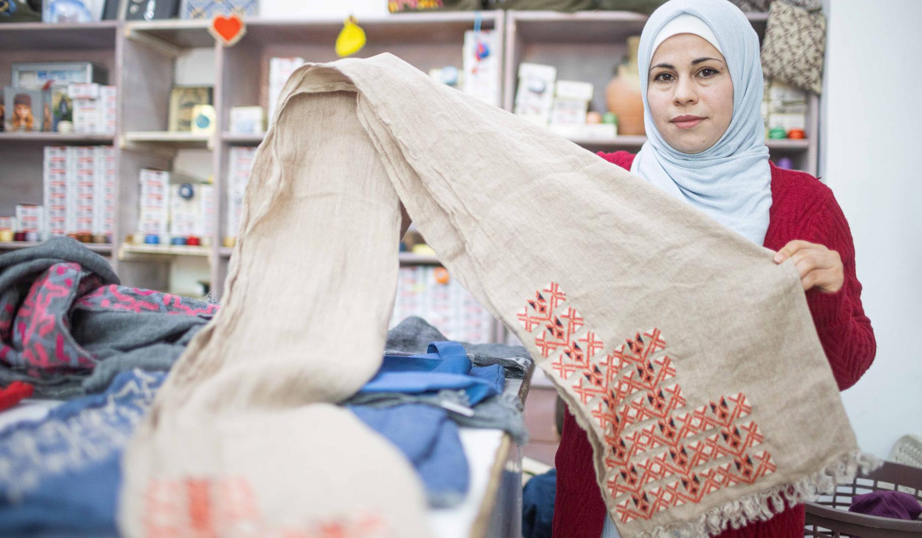 Amal, 33, stands by her work station and holds up fabric.