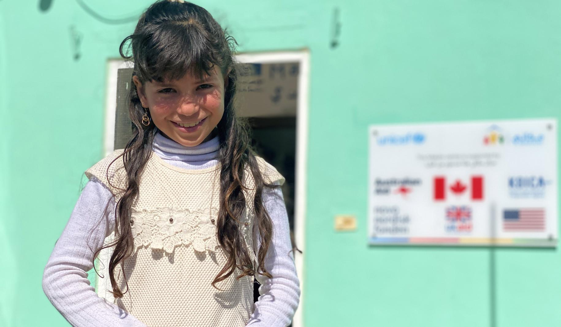 Kawthar, 10, smiles shyly at the camera as she stands outside in front of a green building.