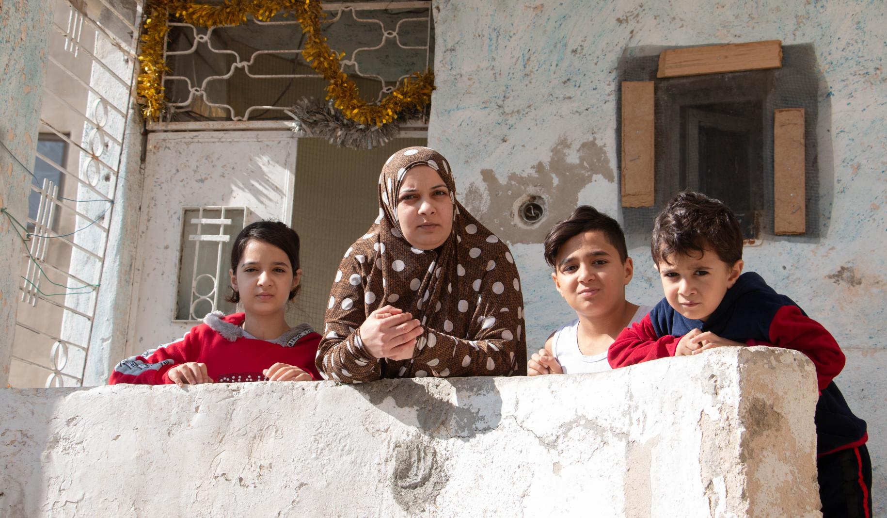 Asma stands with her three children on the porch of their home.