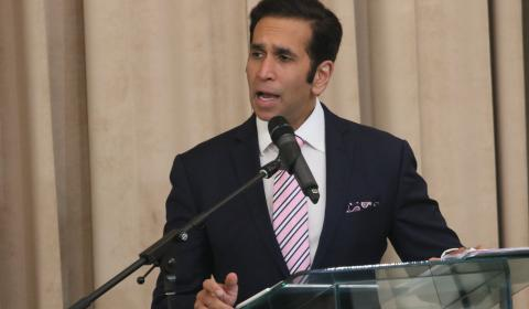 Faris Al-Rawi, Attorney General of Trinidad and Tobago shown speaking into a microphone at a podium on stage.
