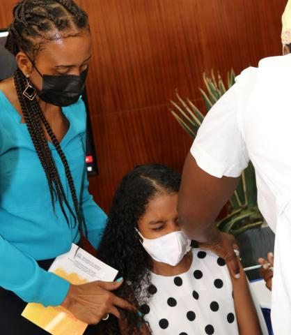 Vicoria Gomes sits in a chair, wearing a face mask as she receives the HPV vaccine on her left arm, while a woman stands to her right of her providing moral support.
